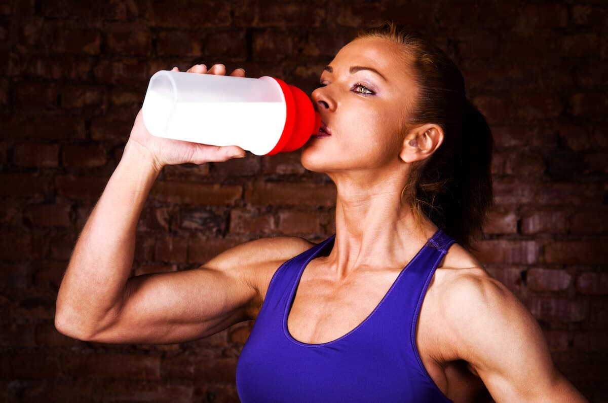 Fit woman drinking from a tumbler