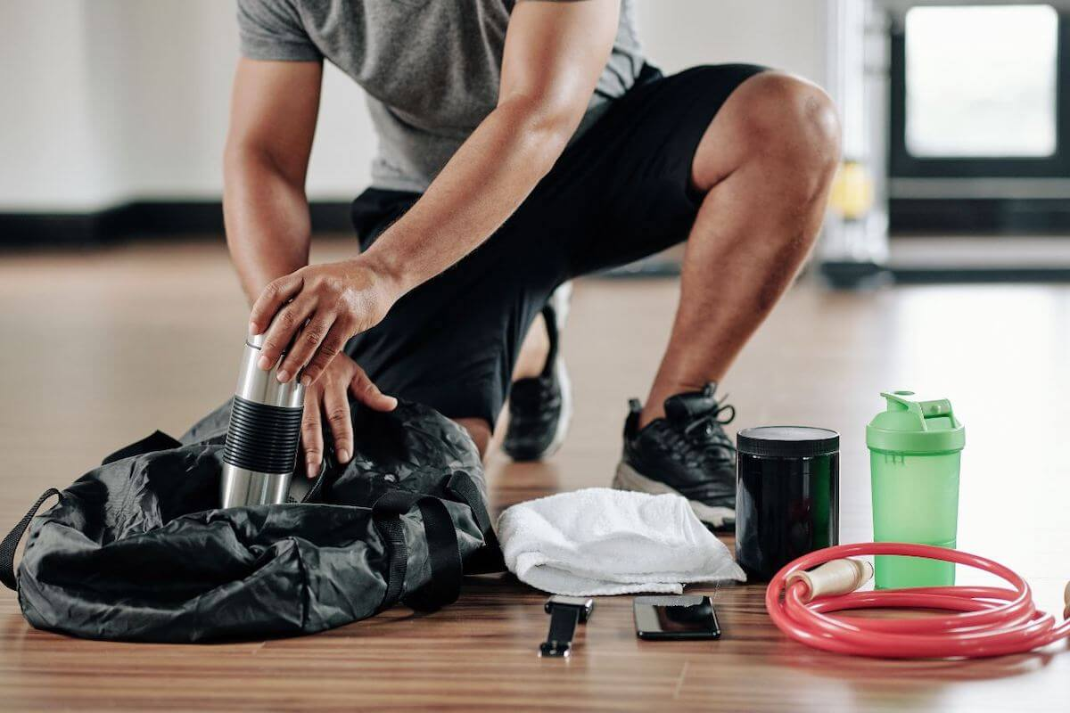 Gym essentials: man getting a tumbler from his bag