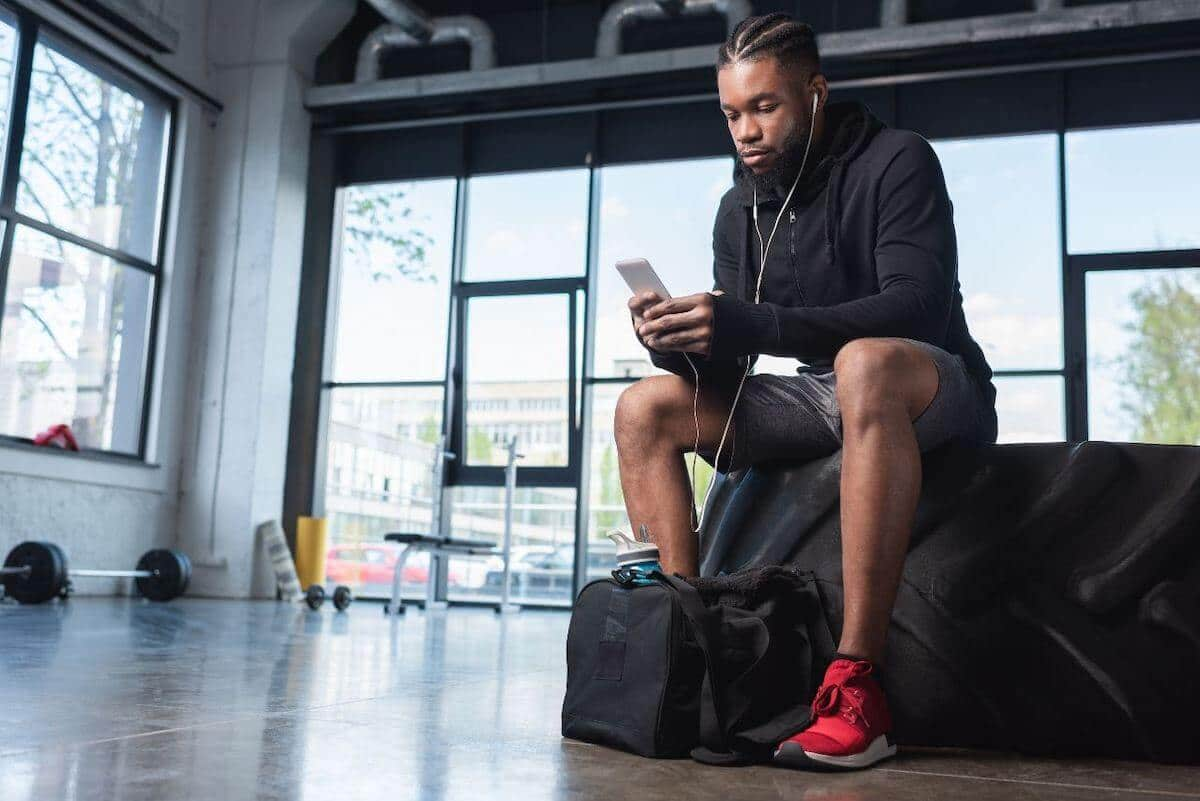 Gym essentials: man listening on his mobile phone