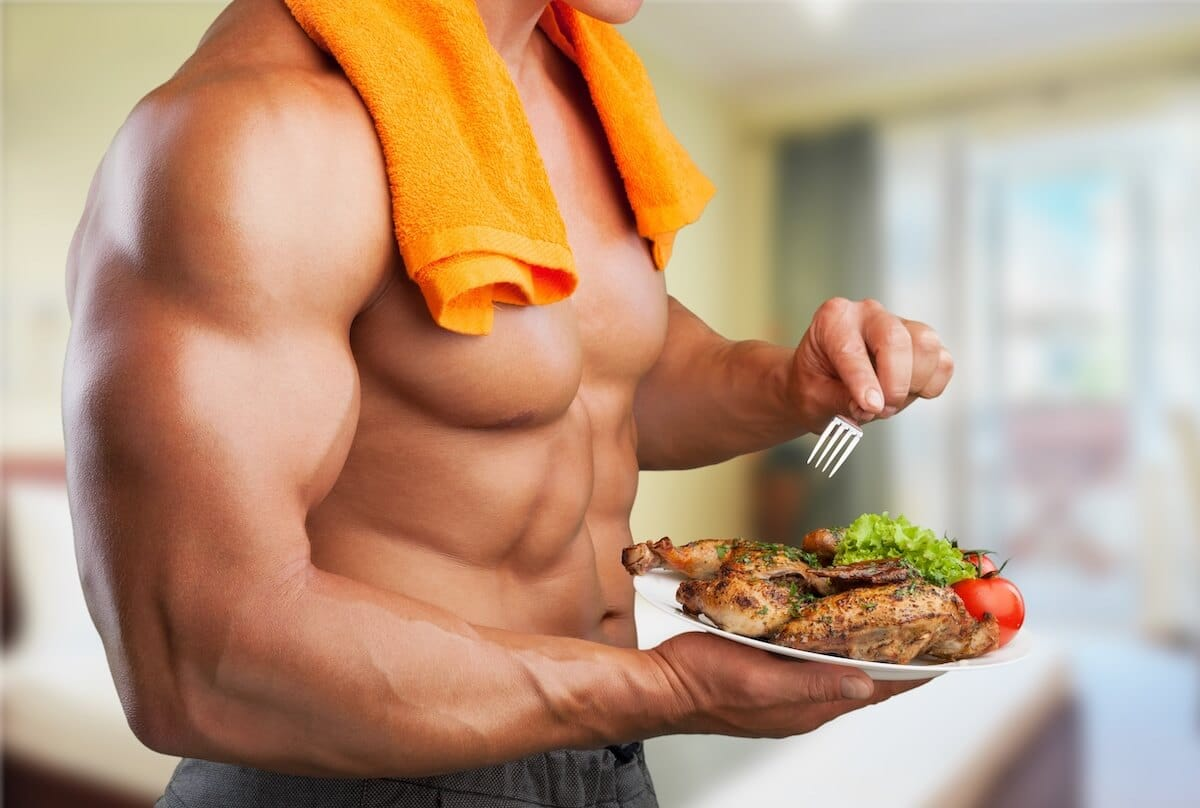How much protein can your body absorb: muscular man eating chicken