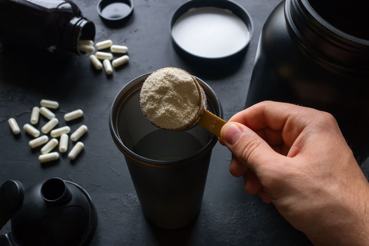 When to take amino acids: person preparing a protein shake, pills scattered in the background