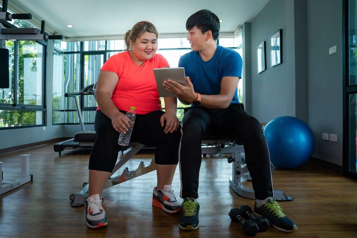 Gym essentials: trainer showing a client something from the tablet