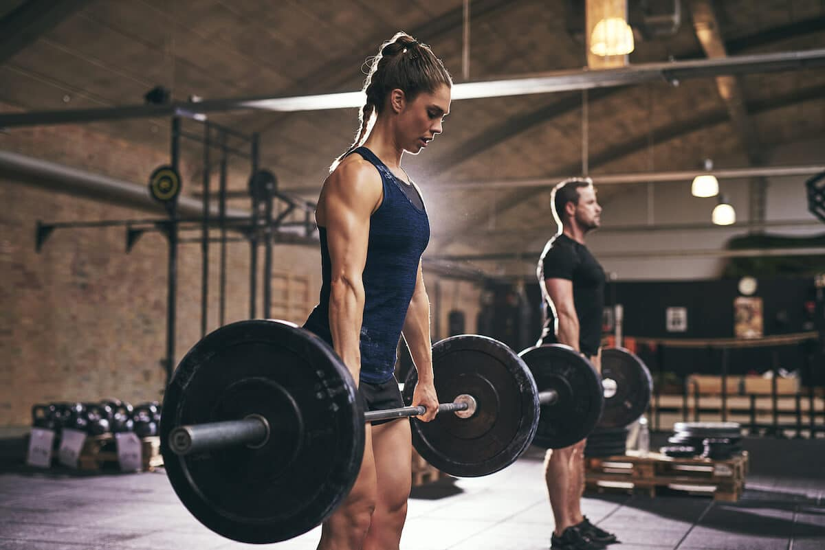 Leucine supplement: two people lifting heavy barbell at the gym
