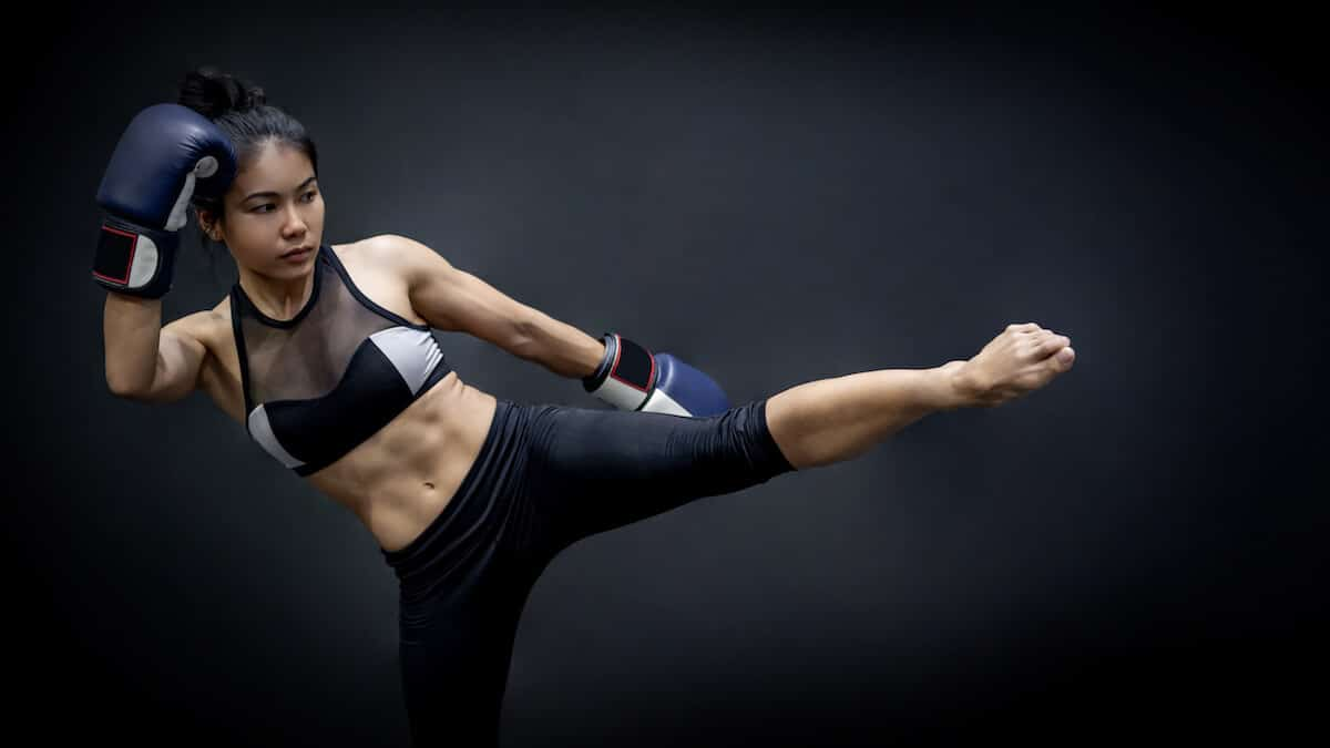 Supplements for athletes: woman kickboxinf