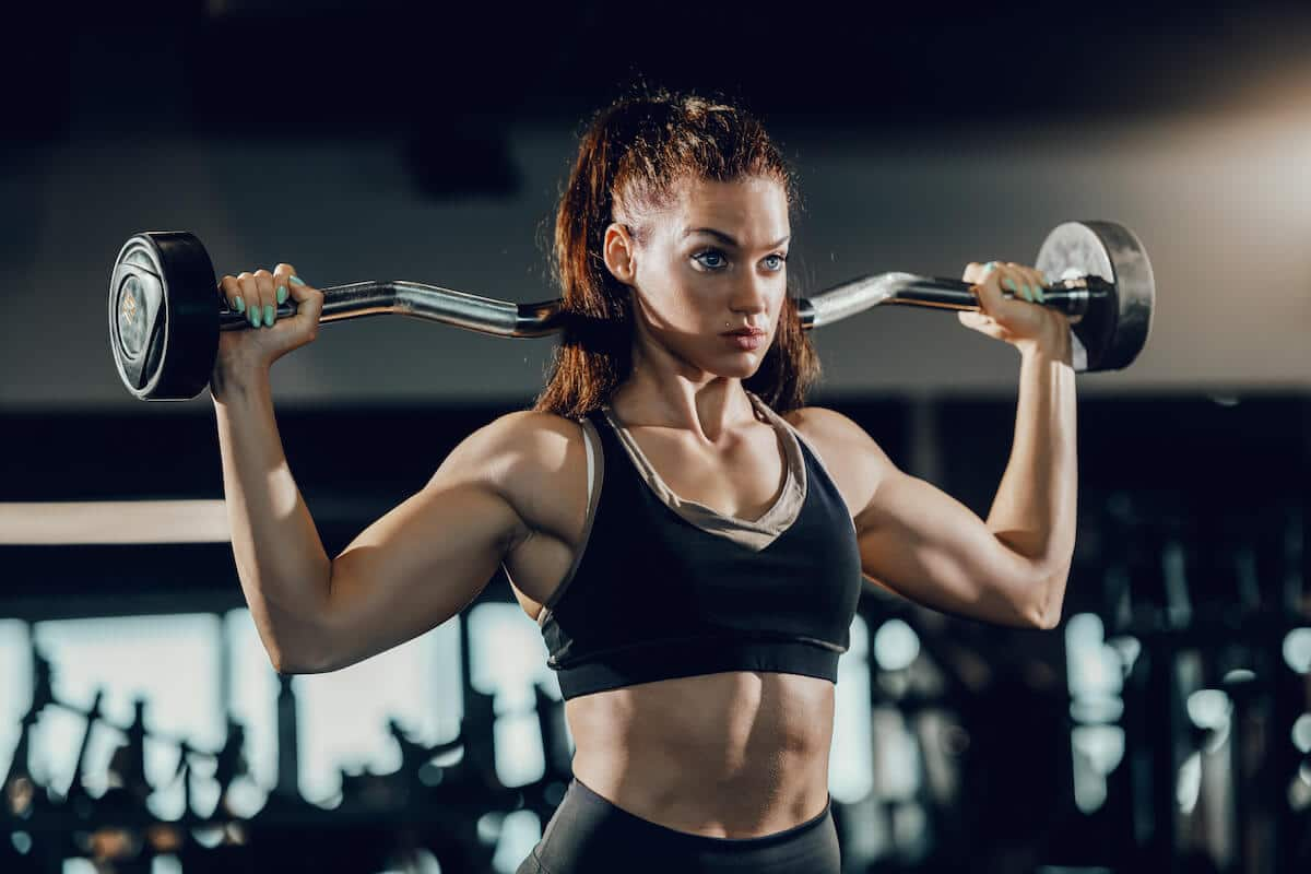 Muscle recovery supplements: woman lifting a barbell