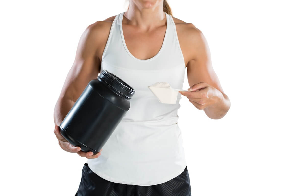 Are BCAAS worth it: athlete taking a scoop of protein powder