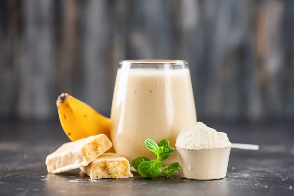 Glass of protein shake, scoop of protein powder, banana and a protein bar